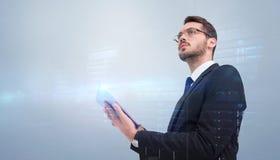 Immagine composita dell'uomo d'affari che distoglie lo sguardo mentre per mezzo della compressa Immagini Stock
