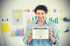 Immagine composita dell'uomo d'affari che mostra compressa digitale con lo schermo in bianco nell'ufficio creativo immagine stock libera da diritti