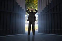 Immagine composita dell'uomo d'affari che sta di nuovo alla macchina fotografica con le mani sulla testa 3d Immagine Stock