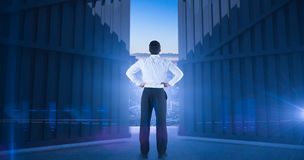 Immagine composita dell'uomo d'affari che sta di nuovo alla macchina fotografica con le mani sulle anche 3d Fotografie Stock Libere da Diritti