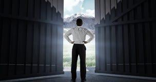 Immagine composita dell'uomo d'affari che sta di nuovo alla macchina fotografica con le mani sulle anche 3d Fotografia Stock Libera da Diritti