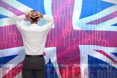 Immagine composita dell'uomo d'affari che sta di nuovo alle mani della macchina fotografica sulla testa Fotografia Stock