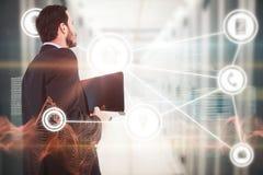 Immagine composita dell'uomo d'affari in computer portatile della tenuta del vestito fotografia stock