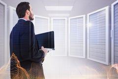 Immagine composita dell'uomo d'affari in computer portatile della tenuta del vestito fotografie stock libere da diritti