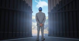 Immagine composita dell'uomo d'affari con il casco che gira il suo di nuovo alla macchina fotografica 3d Fotografia Stock Libera da Diritti
