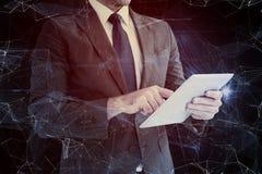 Immagine composita dell'uomo d'affari facendo uso del suo pc della compressa Immagini Stock