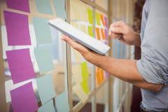 Immagine composita dell'uomo d'affari facendo uso della compressa digitale sopra fondo bianco Immagini Stock