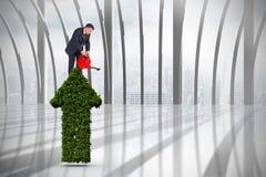 Immagine composita dell'uomo d'affari maturo facendo uso dell'annaffiatoio Fotografie Stock Libere da Diritti