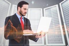 Immagine composita dell'uomo d'affari messo a fuoco facendo uso del suo computer portatile immagini stock libere da diritti