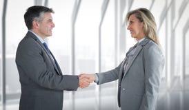 Immagine composita dell'uomo d'affari piacevole che stringe la mano della donna di affari contenta Fotografie Stock Libere da Diritti