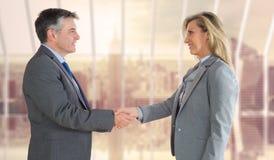 Immagine composita dell'uomo d'affari piacevole che stringe la mano della donna di affari contenta Immagini Stock
