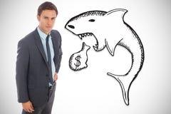 Immagine composita dell'uomo d'affari serio che sta con la mano sull'anca Immagini Stock