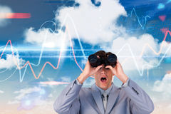 Immagine composita dell'uomo d'affari sorpreso che guarda tramite il binocolo Fotografia Stock