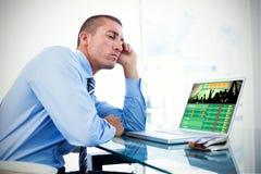 Immagine composita dell'uomo d'affari stanco che esamina il suo computer portatile fotografia stock libera da diritti