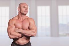 Immagine composita dell'uomo muscolare di misura con le armi attraversate Immagine Stock Libera da Diritti