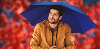 Immagine composita dell'uomo premuroso che sta con l'ombrello Fotografie Stock Libere da Diritti