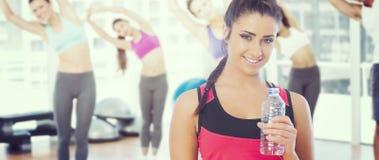 Immagine composita della bottiglia di acqua della tenuta della donna di misura Immagine Stock