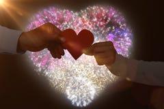 Immagine composita della carta di forma del cuore della carta della tenuta delle coppie Immagini Stock