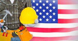 Immagine composita della cinghia d'uso dello strumento del lavoratore manuale mentre tenendo martello e casco Fotografia Stock