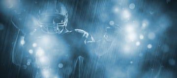 Immagine composita della condizione del giocatore di football americano con il casco che prepara gettare palla immagini stock