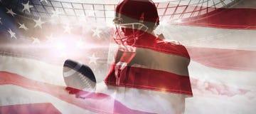 Immagine composita della condizione del giocatore di football americano con la palla ed il casco di rugby immagini stock