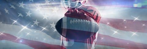 Immagine composita della condizione del giocatore di football americano nel casco di rugby e di tenuta della palla di rugby fotografia stock