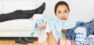 Immagine composita della donna aggrottante le sopracciglia che elimina lavanderia sporca Immagini Stock