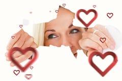 Immagine composita della donna bionda che guarda attraverso la carta lacerata Fotografia Stock