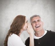 Immagine composita della donna che dice segreto al suo partner Fotografia Stock Libera da Diritti