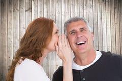 Immagine composita della donna che dice segreto al suo partner Fotografia Stock
