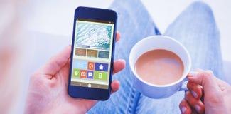 Immagine composita della donna che per mezzo del suo telefono cellulare e tenendo tazza di caffè Fotografia Stock Libera da Diritti