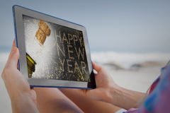 Immagine composita della donna che si siede sulla spiaggia nello sdraio che per mezzo del pc della compressa immagini stock