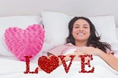 Immagine composita della donna che si trova nel suo letto accanto ad un cuscino rosa del cuore Immagini Stock
