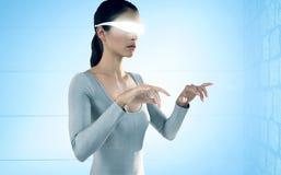 Immagine composita della donna che usando i video vetri virtuali contro il fondo bianco Fotografia Stock