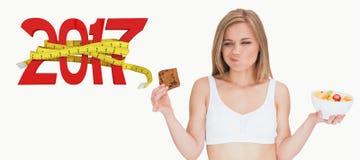 Immagine composita della donna con la ciotola di frutta che fa i fronti come esamina il biscotto Immagini Stock