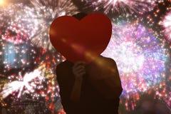 Immagine composita della donna dei pantaloni a vita bassa dietro un cuore rosso Fotografia Stock Libera da Diritti