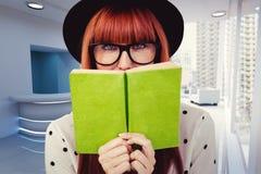 Immagine composita della donna dei pantaloni a vita bassa dietro un Libro verde Fotografia Stock