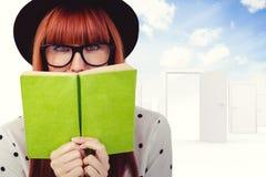 Immagine composita della donna dei pantaloni a vita bassa dietro un Libro verde Immagini Stock