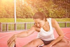 Immagine composita della donna dell'atleta che allunga il suo tendine del ginocchio Fotografie Stock
