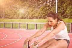 Immagine composita della donna dell'atleta che fa allungando esercizio Immagine Stock Libera da Diritti