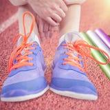 Immagine composita della donna dell'atleta che si siede con le scarpe di sport Immagini Stock Libere da Diritti