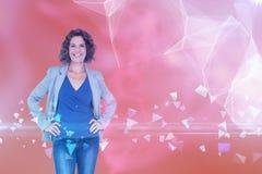 Immagine composita della donna di affari che esamina macchina fotografica con le mani sull'anca Fotografia Stock