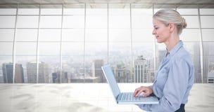 Immagine composita della donna di affari che per mezzo del computer portatile immagine stock libera da diritti