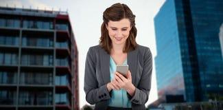 Immagine composita della donna di affari che per mezzo del telefono cellulare Fotografia Stock