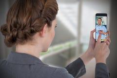 Immagine composita della donna di affari che per mezzo del telefono cellulare Immagini Stock Libere da Diritti