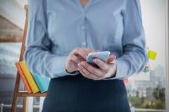 Immagine composita della donna di affari che per mezzo dello Smart Phone fotografia stock libera da diritti
