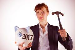Immagine composita della donna di affari che rompe porcellino salvadanaio fotografie stock libere da diritti