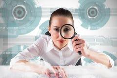 Immagine composita della donna di affari che scrive e che guarda tramite la lente d'ingrandimento Fotografia Stock Libera da Diritti