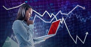 Immagine composita della donna di affari con il dito sulla guancia facendo uso del computer portatile Immagini Stock