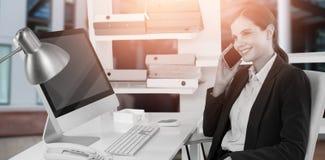 Immagine composita della donna di affari sorridente che parla sul telefono cellulare allo scrittorio con il computer Immagini Stock
